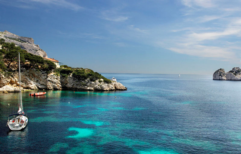 Clear Mediterranean waters just off the coast of Marseille city, small boats bob about, rocky hills line a natural port