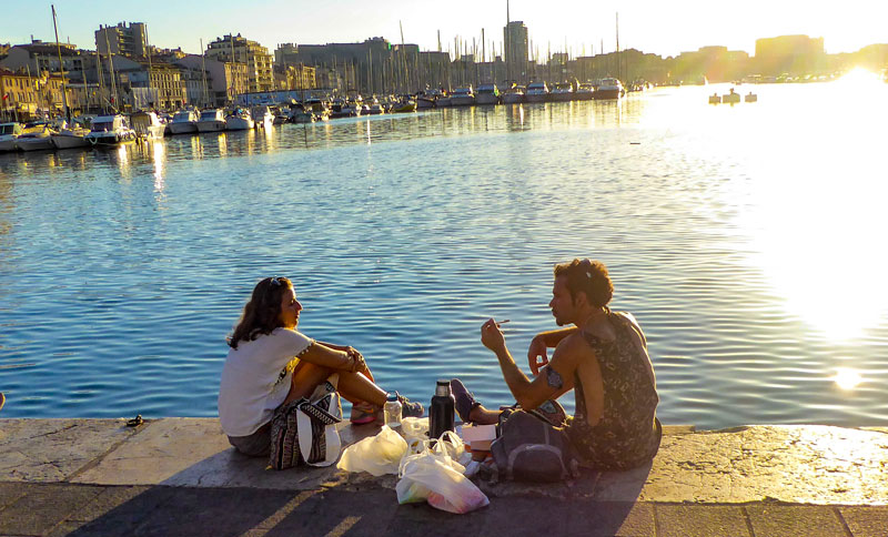 Man and woman sit with a picnic on the quayside of the old port of Marseille at sunset