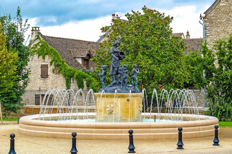 Fountain with a statue of a woman holding a basket of grapes in Meursault, Burgundy