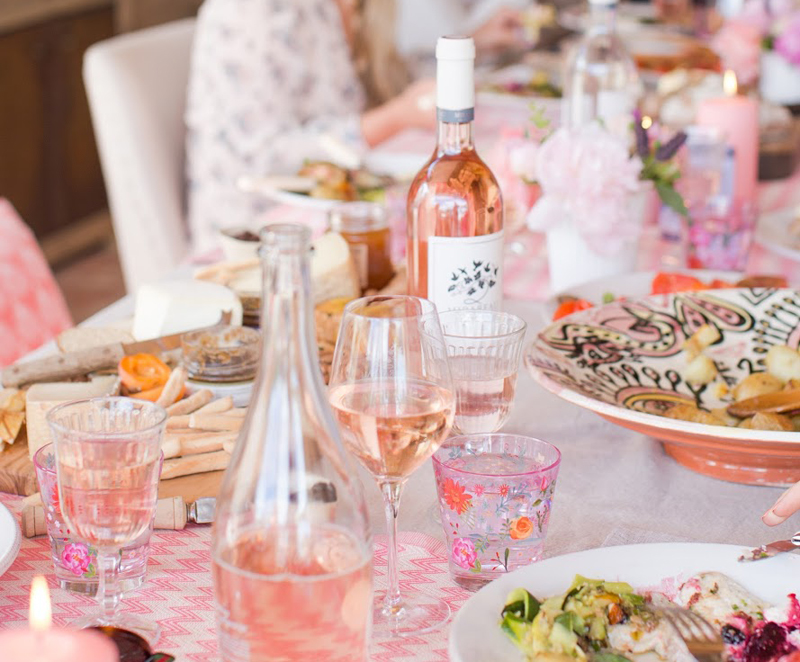 Very pretty table laid with glass and china and bottles of rose wine