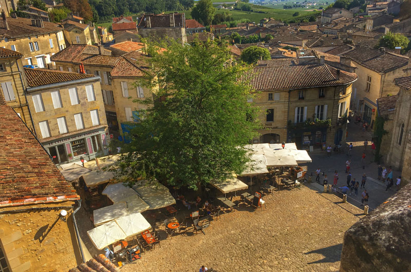 View over Saint Emilion town in Bordeaux, a town square lit by sunlight and many wine bars filled with people