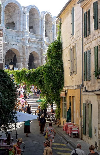 A small street leads to a monumental Roman arena in Arles, Provence
