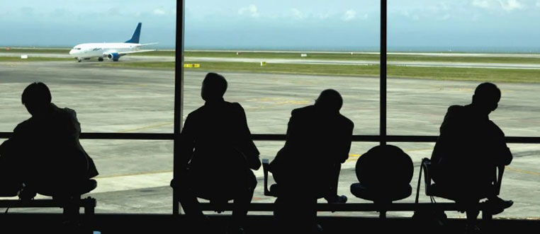 People sitting at an airport watching planes on the runway