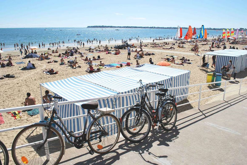 A long golden sandy beach under a blue sky, bikes leaning against railings