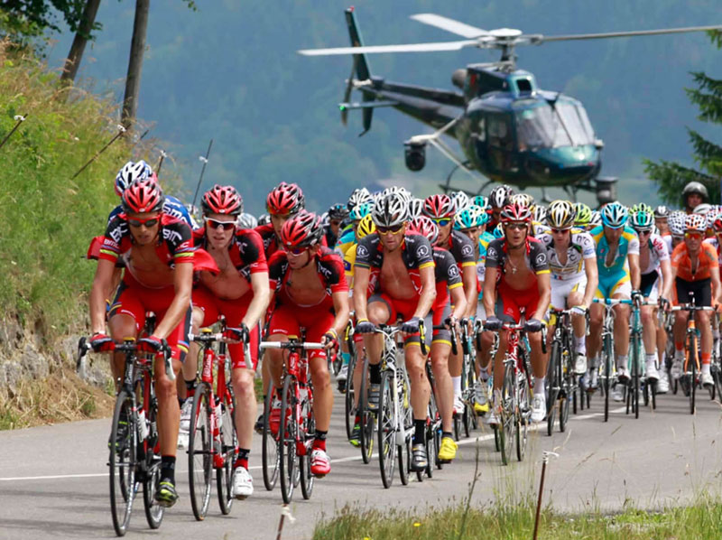 Tour de France riders slogging it out along a steep road, a helicopter swoops low behind to film them