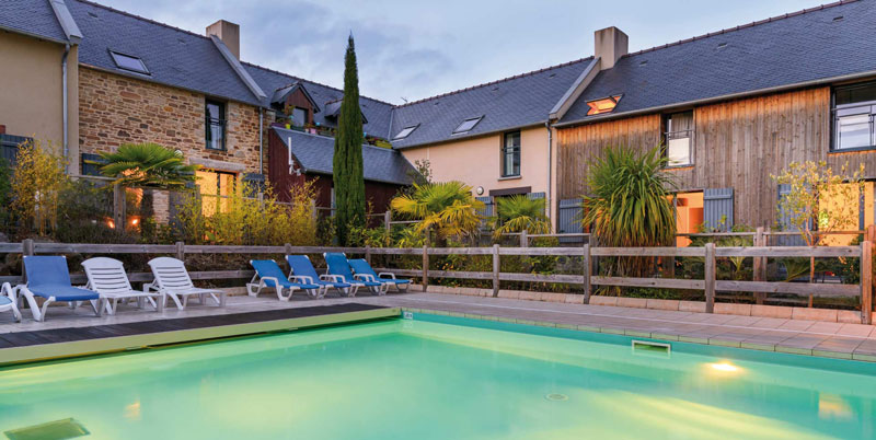 Swimming pool surrounded by pretty holiday cottages in Brittany