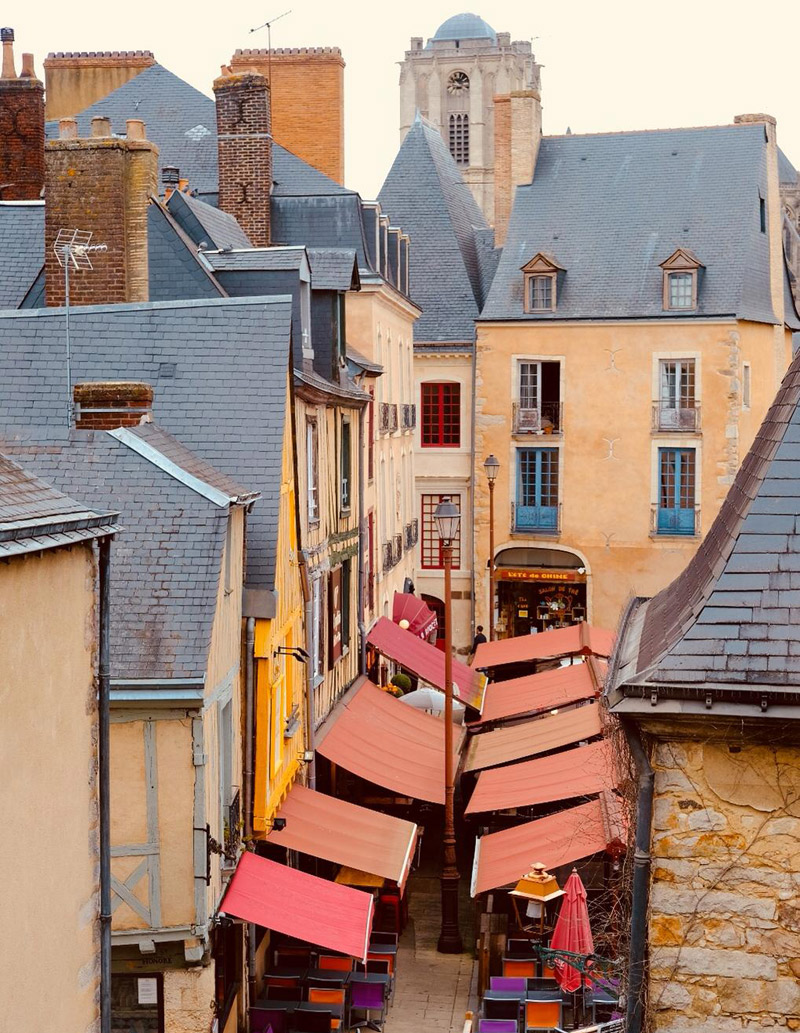 View over the streets of Le Mans with grey slate roofs of mellow stone buildings and colourful red awnings of shops