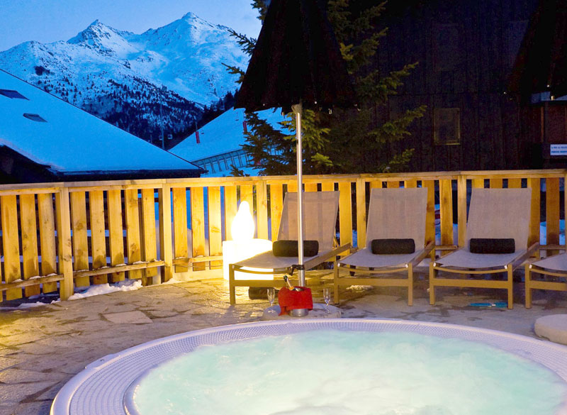 Hot tub on an open terrace overlooking a snowy mountain in Meribel, France