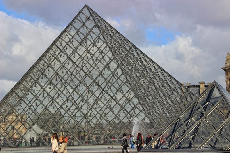 Giant glass pyramid entrance to the Louvre surrounded by basins of water which reflect onto the glass