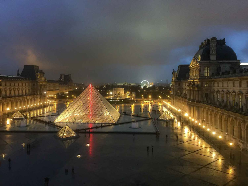 Glass pyramid entrance to the Louvre Museum Paris at night, glowing softly yellow
