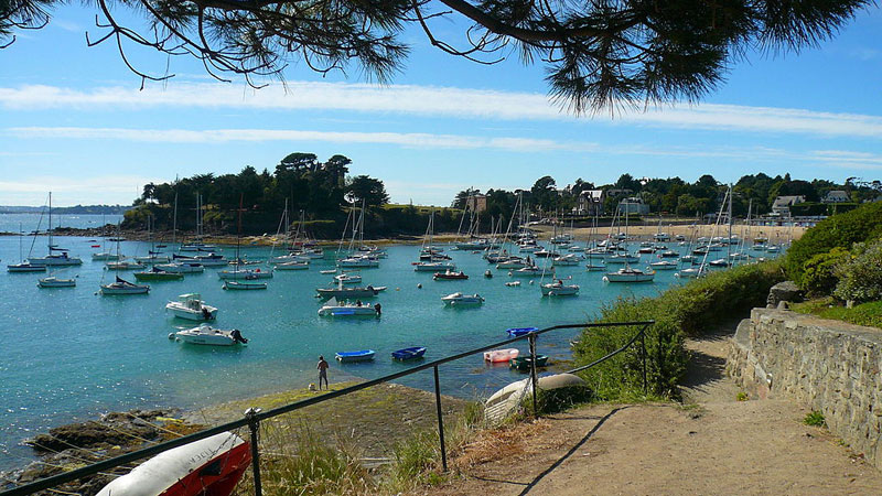 Beautiful and tranquil bay with many boats bobbing up and down on calm waters in Brittany