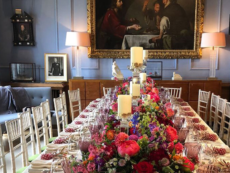 A beautifully decorated dining table in a chateau in Paris, flowers, silver cutlery and linen table cloth
