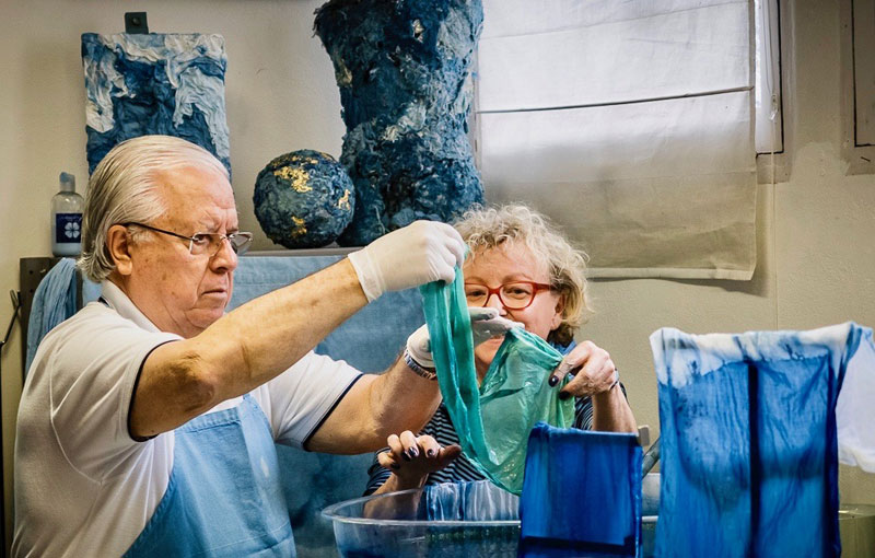 Man and woman holding up cloth pulled from a large vat of blue dye
