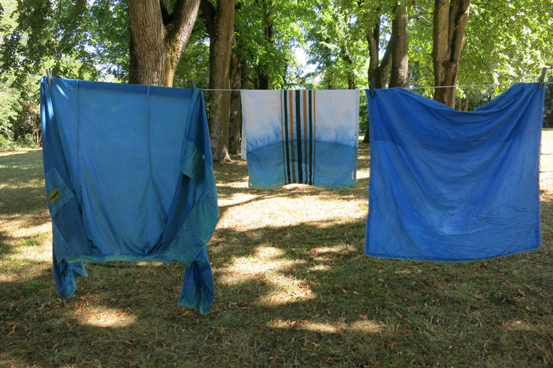 Shirts and cloths dyed blue hang on a line in a garden