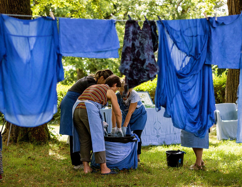 Women hang blue dyed cloth on a line in a garden, working to old methods