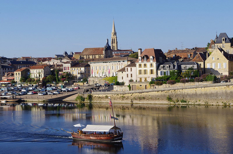 View of the town of Bergerac, buildings like the quayside and a pleasure boat floats serenely on the river