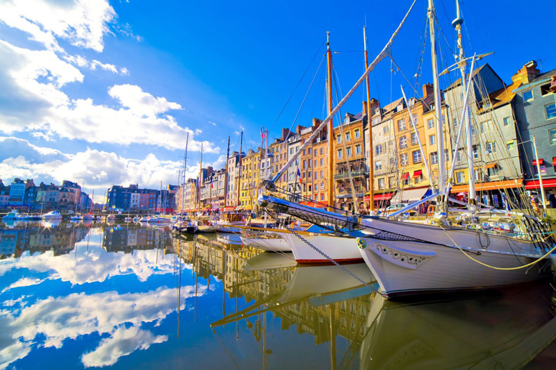 Sunny day at the harbour of Honfleur, Normandy small boats bob up and down, tall buildings line the harbour