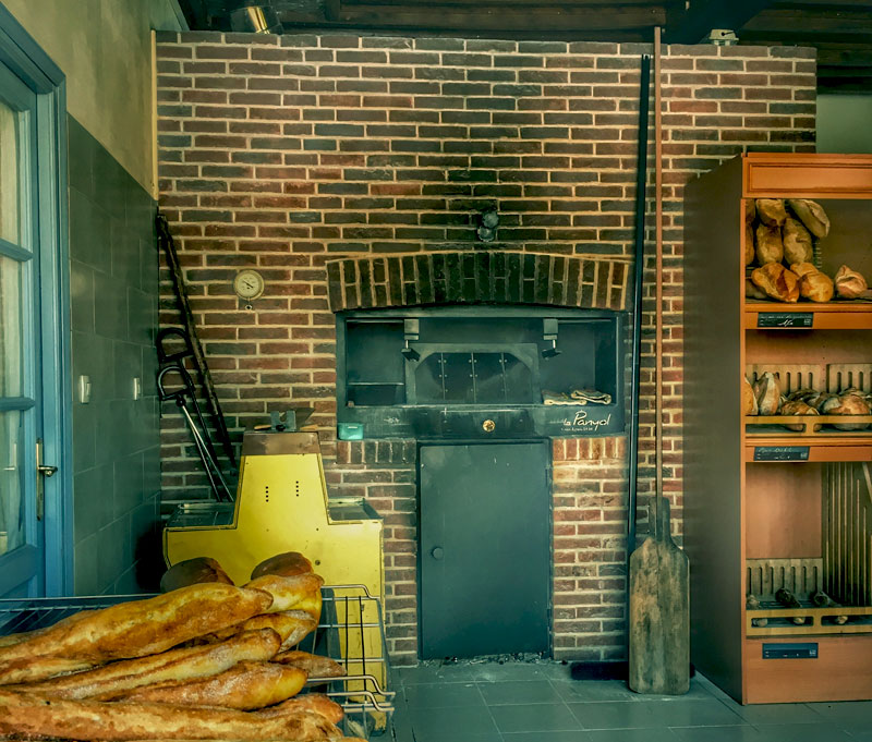 Bread oven in a store in northern France, fresh bread pulled out with a wooden paddle