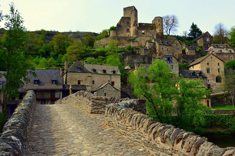 A cobbled bridge over a small river leads to a medieval village in Aveyron, southern France