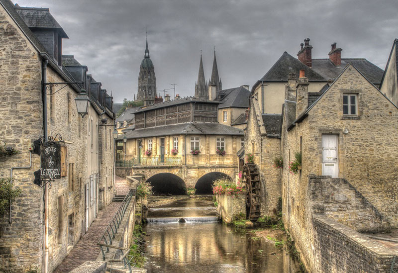 Bayeux town in Normandy, the spires of its Cathedral peeping over ancient houses, a mill wheel turns on a stream
