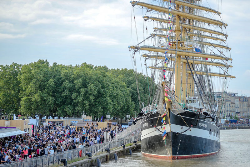 Tall ship docked in Bordeaux, crowds of tourists look in admiration