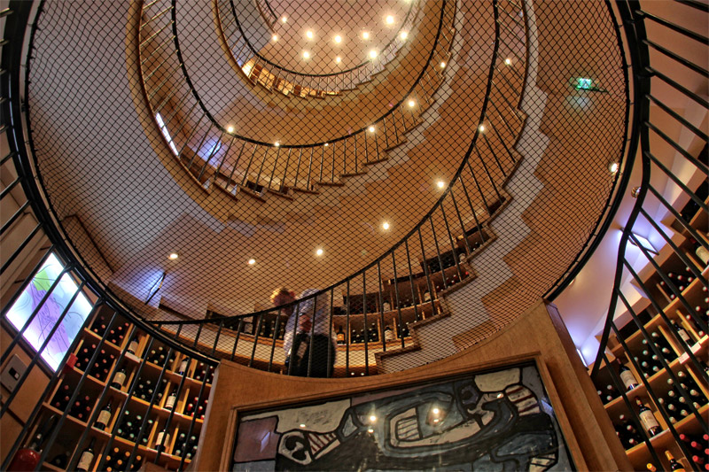 A wine shop in Bordeaux with a spiral stair case running up 5 floors, lined with wine racks