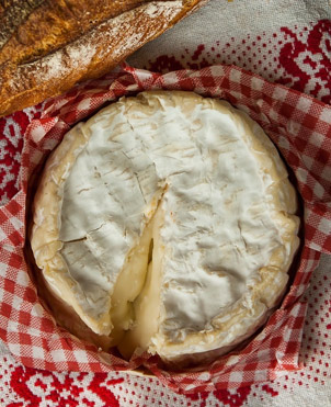Camamber cheese in a basket lined with red and white check cloth