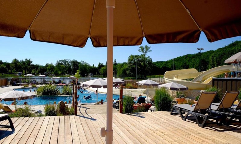 A large sun umbrella at the side of a swimming pool looks like the perfect place to relax in France