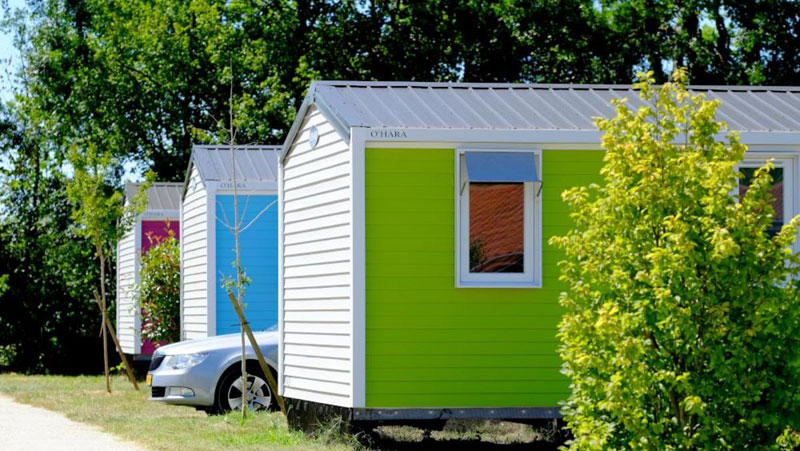 Brightly coloured wooden mobile homes at a campsite in Dordogne