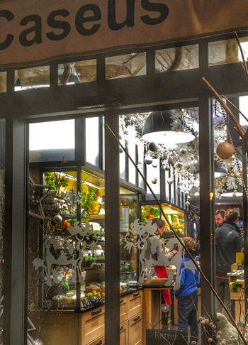 Cheese shop decorated with baubles and fresh flowers, shelves filled with French cheeses