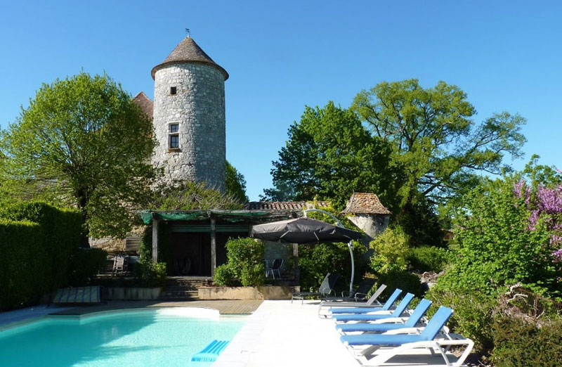 Swimming pool in the grounds of a chateau, sun beds around the side, trees and plants give shade and shelter