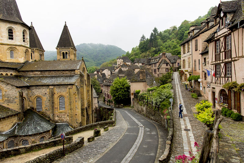 Cobbled streets lined with half-timbered houses and a medieval church in Conques, Aveyron