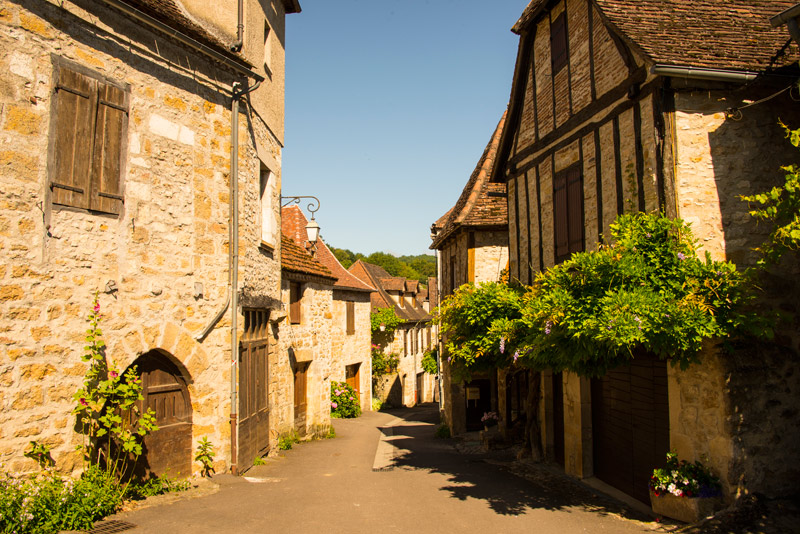Beautiful stone houses in a narrow cobble stone street in Dordogne, southwest France