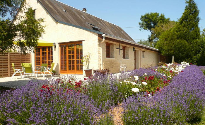 Pretty gite with a garden full of lavender and white and red flowers on a sunny day in Normandy, France