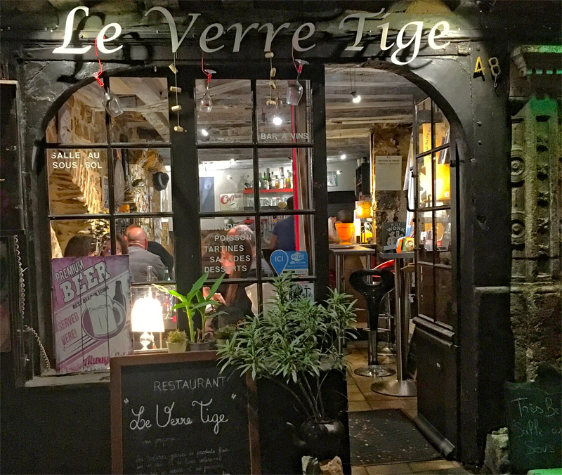 Window of a wine bar at night in Le Mans, a yellow glow from lamps