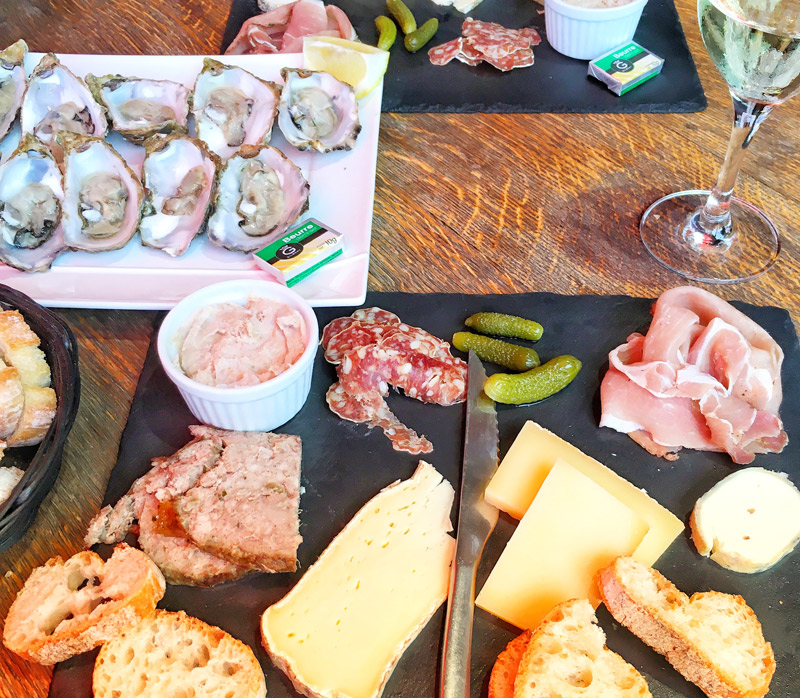 slate tray of oysters, cheese, meets, bread plus glass of wine - a typical French lunch