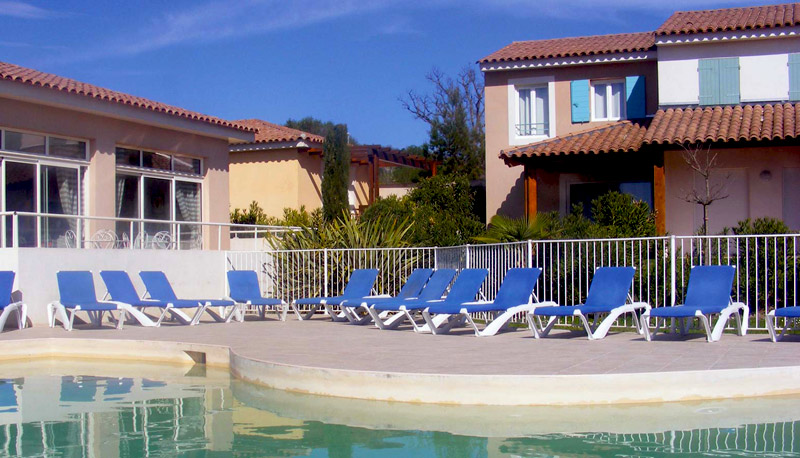 Swimming pool in a holiday resort in Provence, small cottage style holiday homes around it