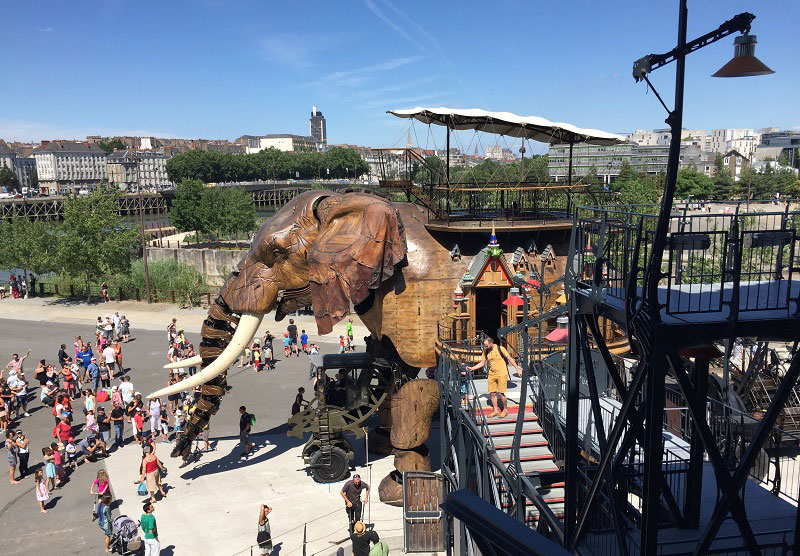 Giant wooden mechanical elephant moves across a large public square at a theme park in Nantes, France