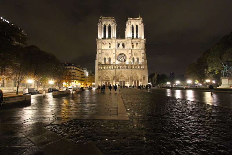 Notre Dame Cathedral at night, the iconic bell towers lit up against a dark sky