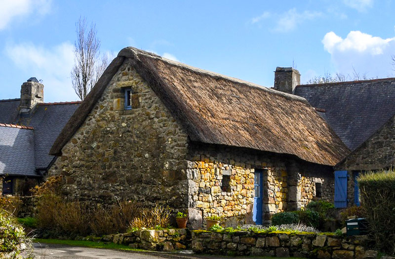 Typical house style of Brittany, thatched roof, stone walls with a small garden