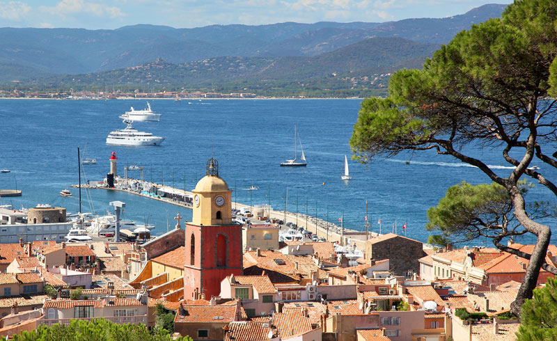 Rooftops of St Tropez at the edge of the Mediterranean Sea, swanky yachts in the background