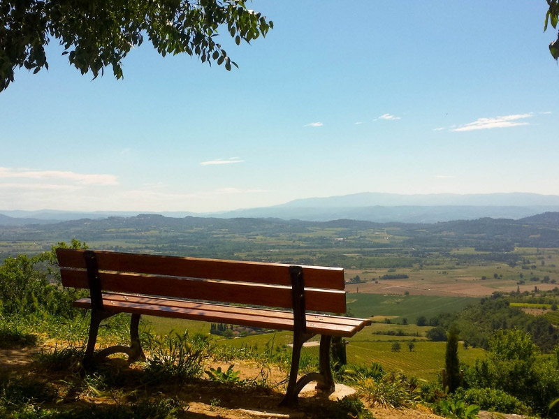 A bench on top of a hill in Provence overlooking beautiful countryside