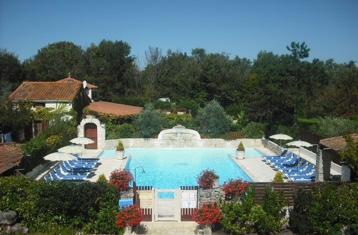 swimming pool surrounded by sun beds with sun umbrellas, lots of trees give shade