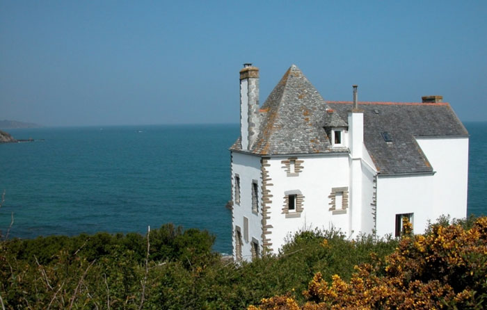 Beautifu white house with pointy roof right on the edge of a beach overlooking the ocean in Brittany