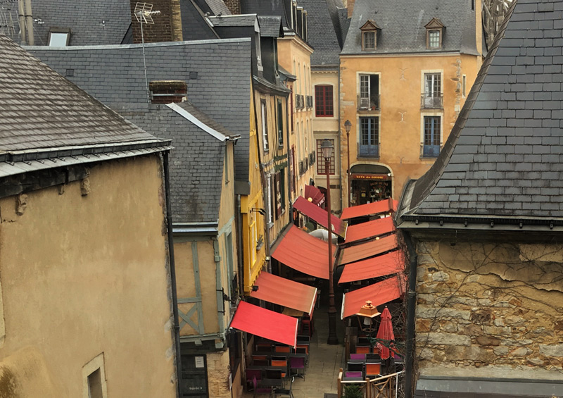 View from a high window of a cobbled street in Le Mans, colourful awnings cover restaurants