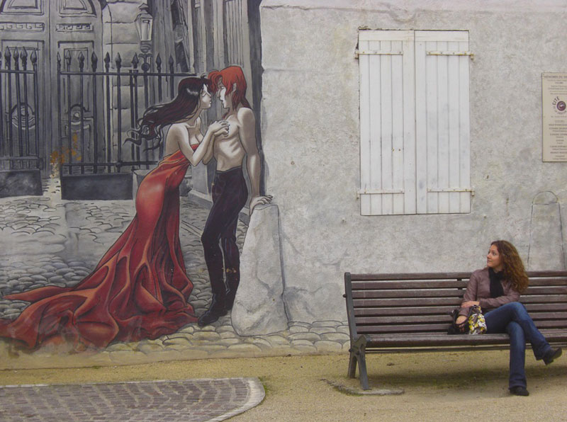 Woman sits on a bench admiring a wall mural in Angouleme in Charente, France