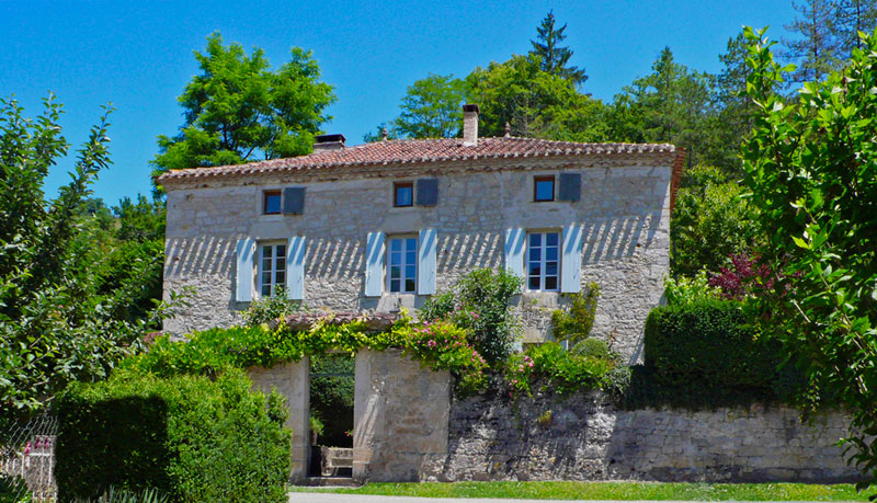 Beautiful stone house with white shutters and rose covered walls