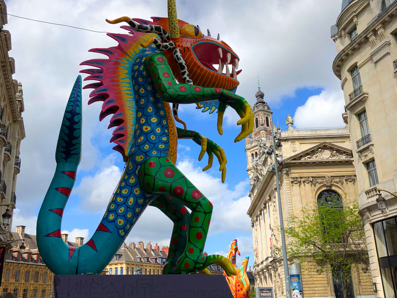A giant paper mache dragon figurine towers over the streets of Lille for the Lille3000 Eldorado art festival