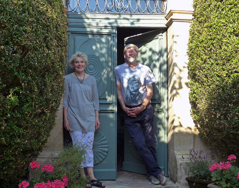 Man and woman stand on the doorstep of their pretty house looking proud