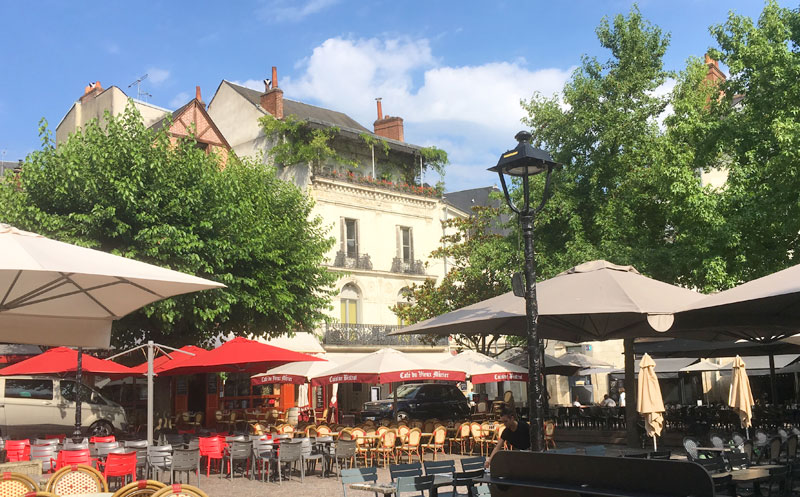 Colourful umbrellas over tables set out in Place Plumereau, a popular square for aperitifs in Tours, Loire Valley